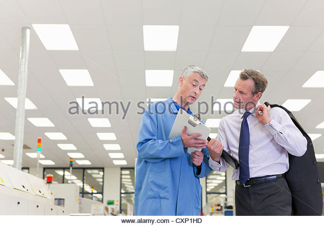 Engineer and manager looking down at clipboard in hi-tech electronics factory - Stock Image
