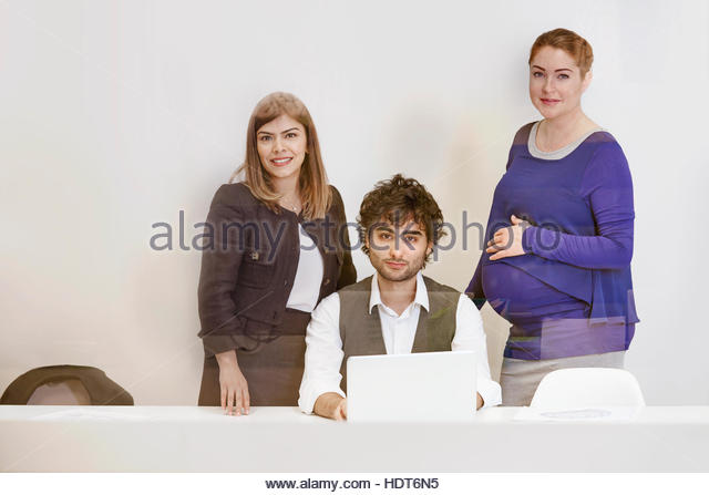 Businesspeople discussing work behind window. - Stock Image