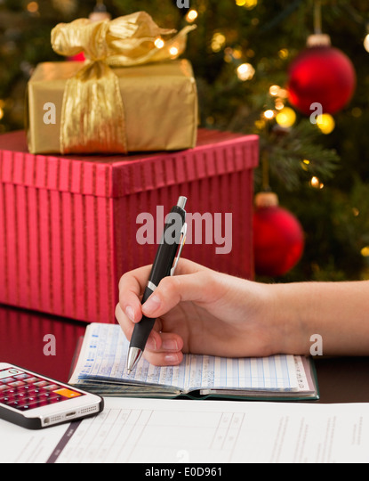 Teenage girl (14-15)  with cheque book buying gifts for Christmas - Stock-Bilder