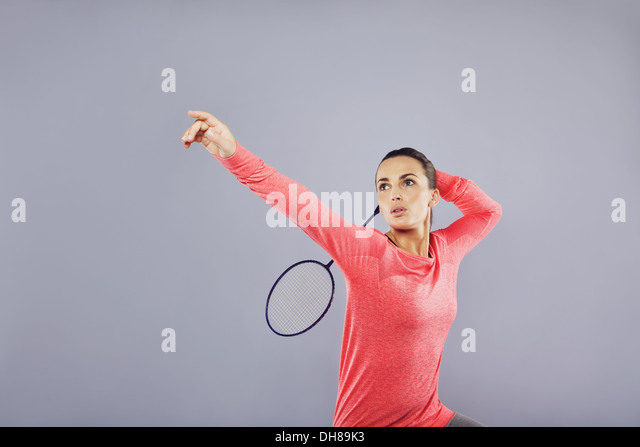 Beautiful young female playing badminton on grey background. Attractive caucasian woman badminton player with lots - Stock Image