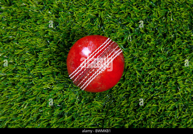 Photo of a red leather cricket ball with stitched seams on grass - Stock Image