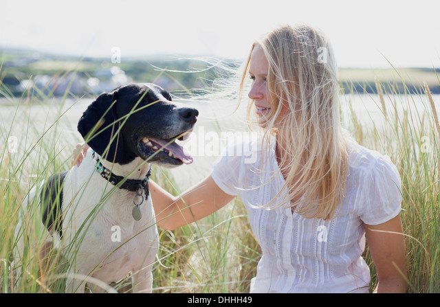 Woman with dog by coast, Wales, UK - Stock Image