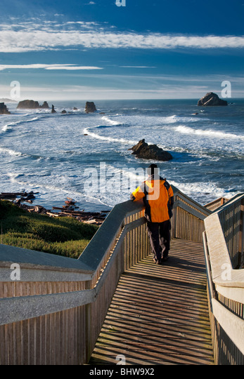 Tourist viewing ocean on stairs leading to beach at Bandon, Oregon. - Stock Image