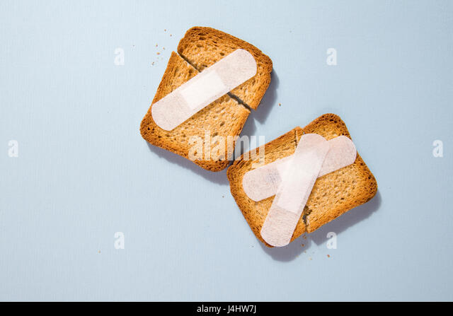 Repair a broken rusk with a plaster medical on a blue background - Stock Image