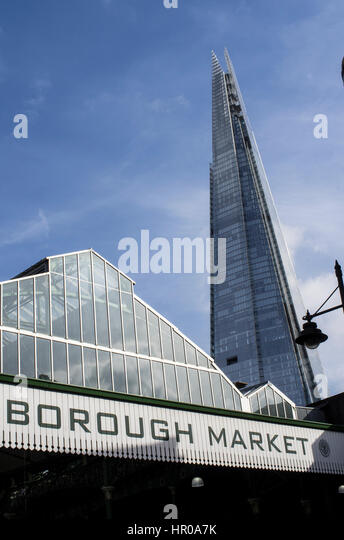 Roof of Borough Market with signage and the Shard in the background against a blue sky with wisps of clouds - Stock Image