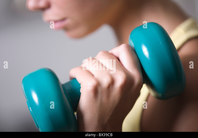 close-up of young woman exercising with dumb bell - Stock-Bilder