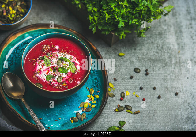 Spring detox beetroot soup with mint, chia, flax and pumpkin seeds on bright blue ceramic plate over grey concrete - Stock Image