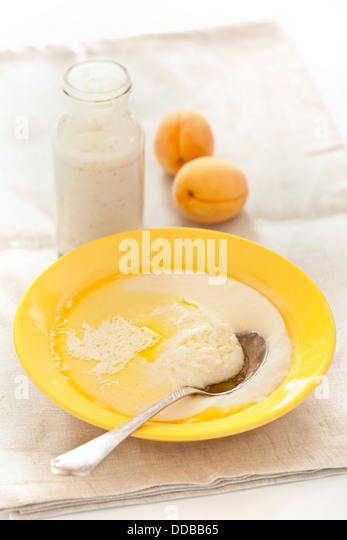 Bowl of porridge with peach and yoghurt on textured background - Stock Image