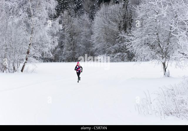 A jogger running through a snowy landscape. - Stock-Bilder