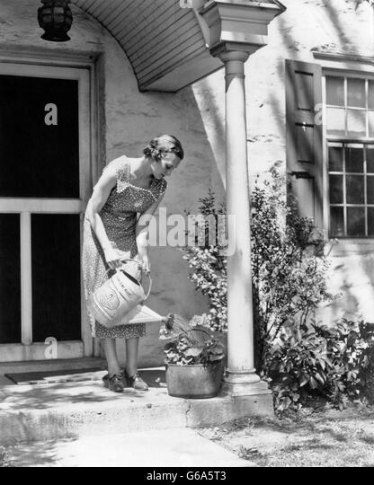 1930s WOMAN WEARING PRINT DRESS WATERING POTTED PLANT WITH WATERING CAN ON FRONT STOOP OF HOUSE - Stock Image