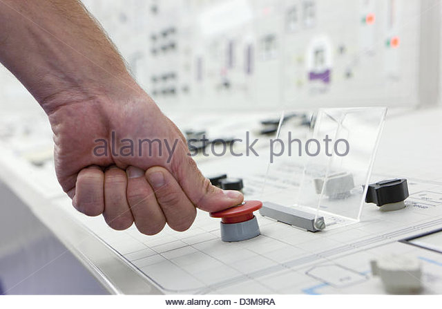 Close up of man pushing red emergency button on control panel - Stock Image