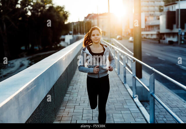 Beautiful female jogging in city and keeping her body in shape - Stock-Bilder
