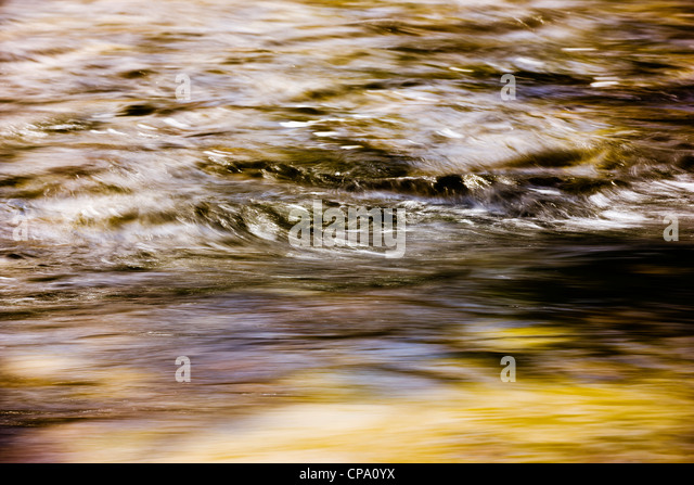 Blurred motion close up photograph of the Arkansas RIver running through the historic district of the small town - Stock Image
