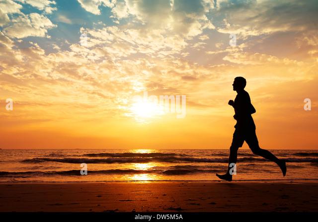 silhouette of man running on the beach at sunset - Stock-Bilder