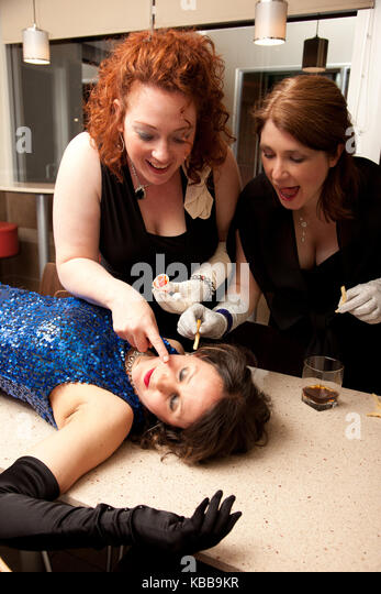 girls dressed up fancy paint ketchup and french fries prank on their passed out friend - Stock Image