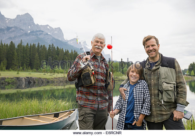 Three generations of men standing by still lake - Stock Image
