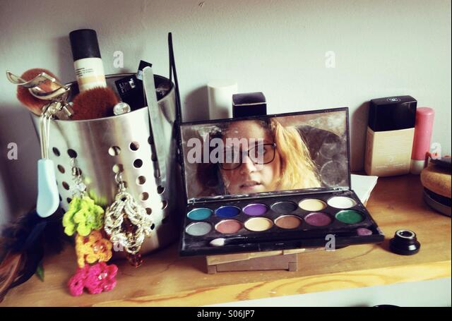Reflection of a girl in her makeup set - Stock Image