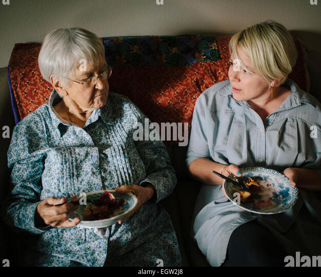 Younger woman and senior woman eating pie together on sofa. - Stock-Bilder