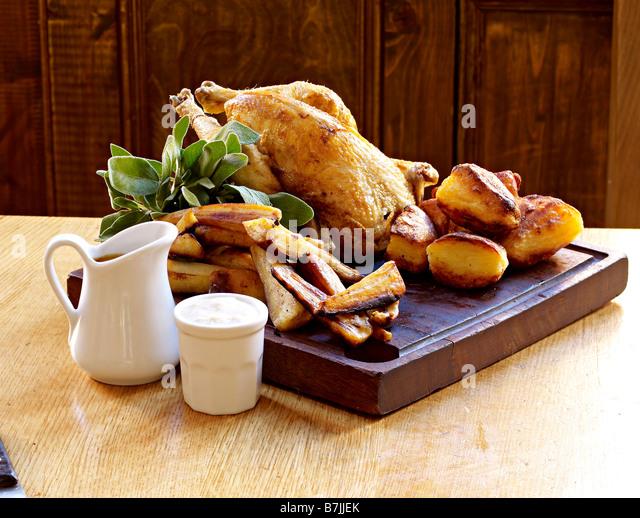 roast chicken roast potatoes roast parsnips - Stock Image
