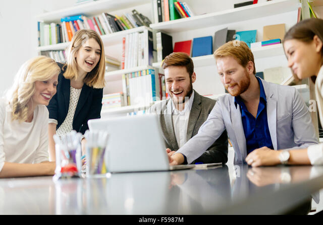 Team of creative people and designers in office smiling and being creative - Stock Image