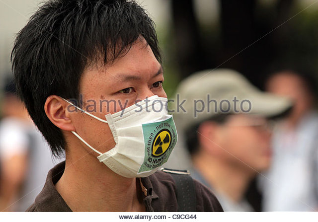 A protester wearing an anti-nuclear facemask marches in the 'Energy Shift Parade' in Shibuya, following - Stock Image