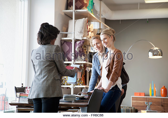 shopkeeper showing choices to couple - Stock Image