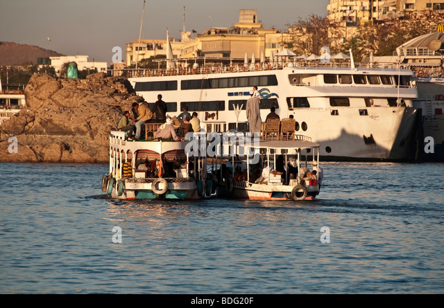 Aswan small passenger ferry boats Nile River Aswan Egypt traditional transport vessel nile cruise ship background - Stock Image