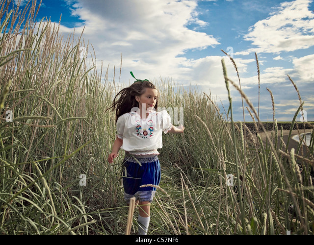 Girl running in wheat field - Stock Image