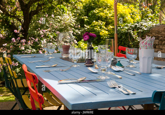 Brightly coloured furniture outside for al fresco dining at lunch time - Stock Image