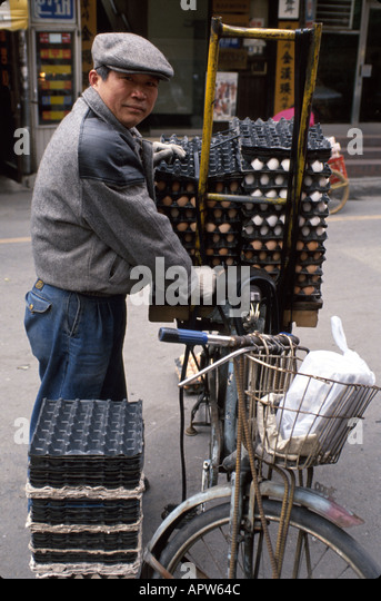 South Korea Asia Far East Seoul Asian man bicycle egg crates delivery winter - Stock Image