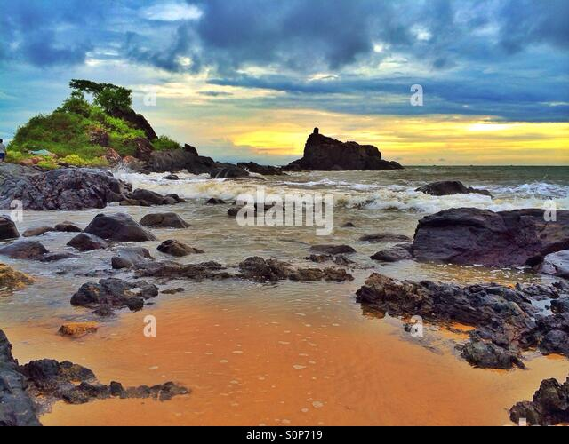 Trees, rocks, sea, sand and sky landscape - Stock Image