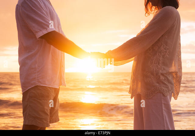 Romantic Mature Senior Couple Holding Hands Enjoying at Sunset on the Beach - Stock Image