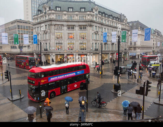 Shoppers in a deserted Oxford Circus as heavy rain pours down - Stock Image