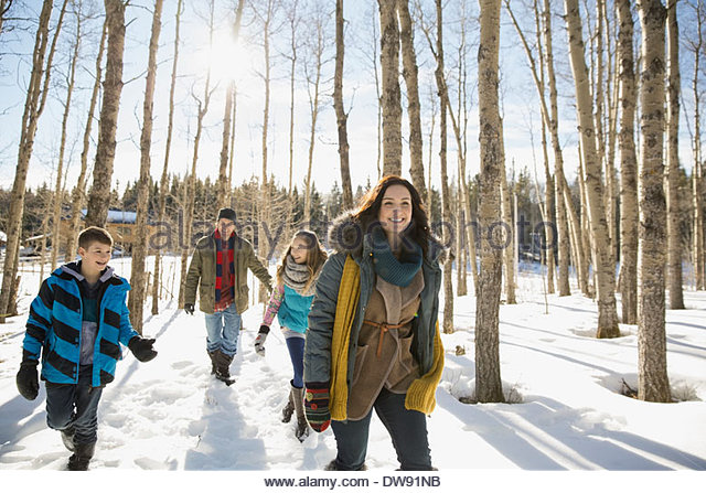 Family walking through winter forest - Stock Image