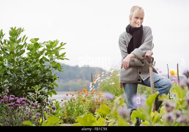 Portrait of mid adult woman digging in organic garden - Stock Image