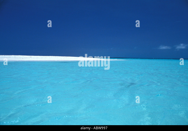 Tropical beach with bright clear water and spit of sand dark blue sky ideal perfect tropical vacation hideaway - Stock Image