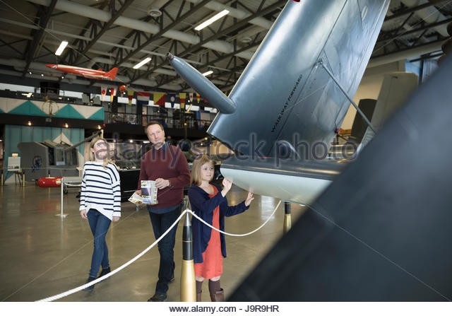 Curious family looking at wing of airplane in warm museum hangar - Stock-Bilder