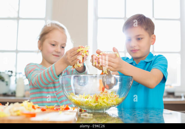 Brother and sister preparing salad in kitchen - Stock Image