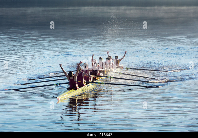 Rowing team celebrating in scull on lake - Stock Image