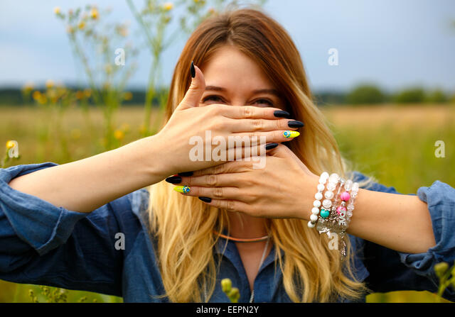 Girl covers her face with her hands - Stock Image