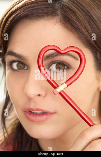 Woman holding heart shape pencil - Stock Image