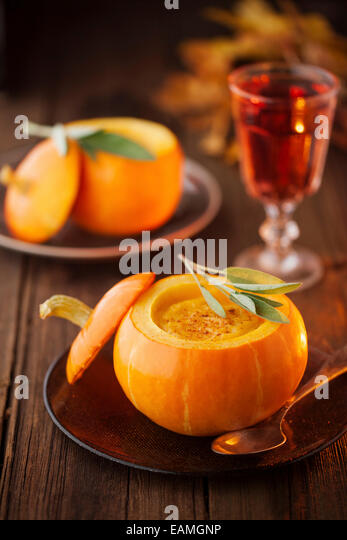 Pumpkin soup in a small pumpkin with leaf of sage - Stock Image