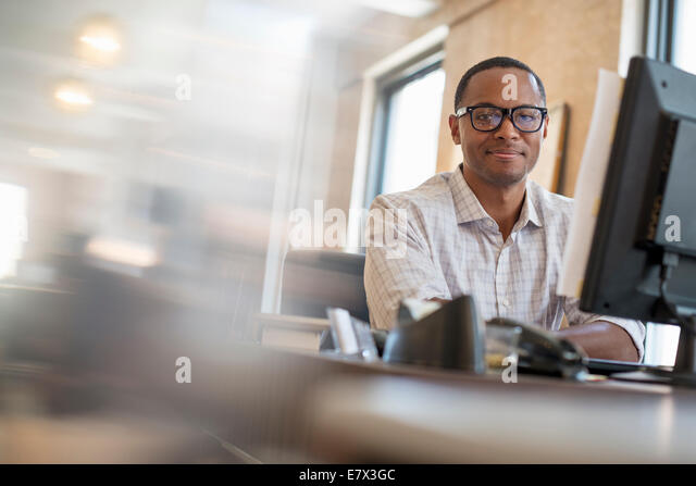 Office life. A man seated at a desk using a computer. - Stock Image