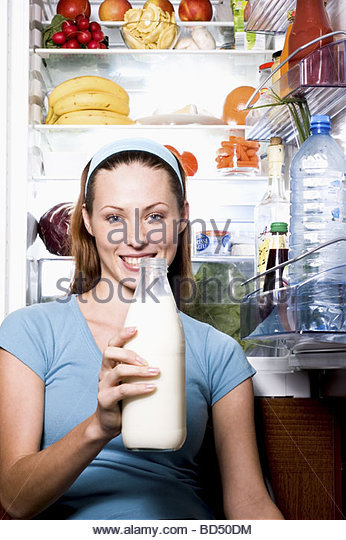 Young woman with milk bottle in front of open fridge - Stock Image