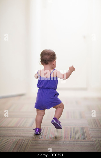 Toddler girl learning to walk - Stock Image