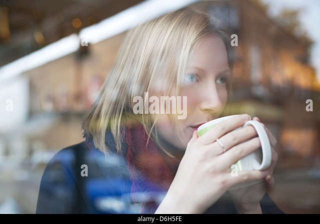 Woman drinking cup of coffee in cafe - Stock-Bilder
