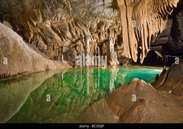 Stalagmites stalactites and subterranean lake. Krizna Jama karst cave system. Loska Dolina. Slovenia - Stock Image