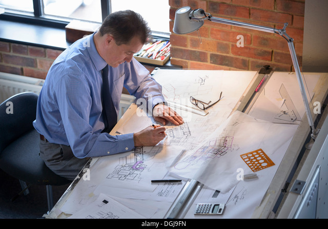 Architect drawing plans at drawing board - Stock-Bilder