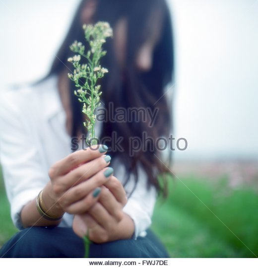 Close-Up Of A Woman Holding Plant - Stock Image