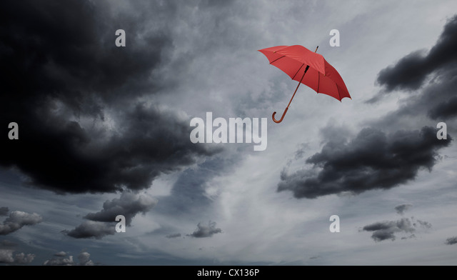 Red umbrella floating through cloudy sky - Stock Image